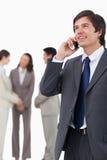 Vendedor que habla en el teléfono móvil con el equipo detrás de él Imagen de archivo libre de regalías