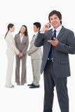 Vendedor que habla en el teléfono móvil con el equipo detrás de él Fotografía de archivo