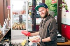 Vendedor que hace el perrito caliente en snack bar de los alimentos de preparación rápida Imagenes de archivo
