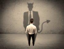 Vendedor que hace frente a su propia sombra del diablo Fotografía de archivo libre de regalías