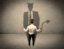 Vendedor que hace frente a su propia sombra del diablo Fotos de archivo libres de regalías