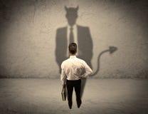 Vendedor que hace frente a su propia sombra del diablo Imagenes de archivo