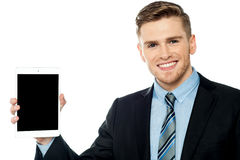 Vendedor que indica o dispositivo novo da tabuleta Imagens de Stock