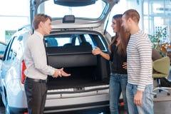 Vendedor que indica o tronco do carro aos clientes Imagens de Stock