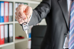 Vendedor que lleva a cabo llave del coche Imagen de archivo libre de regalías