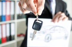 Vendedor que lleva a cabo una llave y que muestra un diseño del coche Imágenes de archivo libres de regalías