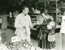 Vendedor que negocia con la mujer en el mercado Foto de archivo