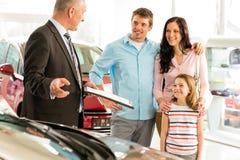 Vendedor que ofrece un coche a la familia Fotografía de archivo libre de regalías