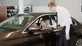 Vendedor que presenta el coche ejecutivo de la clase a la mujer dentro del sitio de la demostración almacen de metraje de vídeo