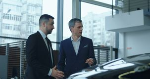 Vendedor que presenta el nuevo coche al cliente potencial almacen de metraje de vídeo