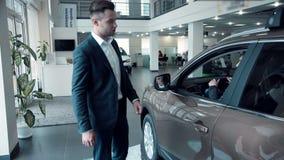 Vendedor que presenta un nuevo coche eléctrico a un cliente almacen de metraje de vídeo