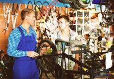 Vendedor que repara la rueda de la bici y que charla al muchacho Imágenes de archivo libres de regalías