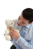 Vendedor que sostiene un oso de peluche Imágenes de archivo libres de regalías
