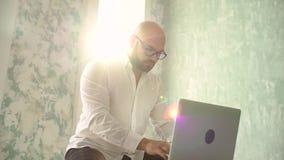 Vendedor que trabaja en oficina con el ordenador portátil Hombre de negocios o encargado que trabaja en el ordenador portátil el  almacen de metraje de vídeo