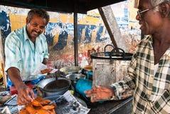 Vendedor que vende la comida en un mercado local Fotos de archivo libres de regalías