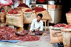 Vendedor que vende la pimienta de chile rojo en sacos en el mercado callejero Foto de archivo libre de regalías