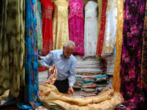 Vendedor que vende vestidos nos souks marroquinos Fotografia de Stock Royalty Free