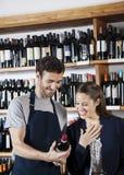Vendedor Showing Wine Bottle al cliente femenino feliz Fotografía de archivo libre de regalías