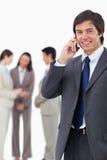 Vendedor sonriente en el teléfono móvil con el equipo detrás de él Imagenes de archivo