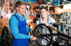 Vendedor sonriente que repara la rueda y la charla de la bici Fotografía de archivo