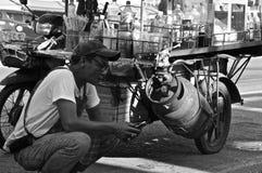 Vendedor tailandés del café que comprueba el teléfono Imágenes de archivo libres de regalías
