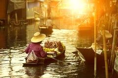 Vendedor tailandês do fruto que navega o barco de madeira no mercado de flutuação da tradição de Tailândia foto de stock