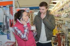 A vendedora ajuda o cliente na loja de ferragens fotografia de stock royalty free