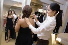 Vendedora Assisting Female Customer com vestido Imagem de Stock