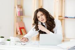Vendedora bem vestido séria que fala no telefone no escritório atrás de seus mesa e laptop Copie o espaço foto de stock