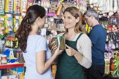 Vendedora de sorriso Looking At Customer que guarda o frasco do alimento para cães Foto de Stock Royalty Free