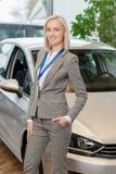 A vendedora está levantando na frente do carro extravagante Imagens de Stock