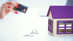 A vendedora guarda um cartão de crédito e o cálculo de um preço de vender o empréstimo hipotecario novo Casa privada modelo e cha fotografia de stock royalty free