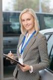 Vendedora no salão de beleza do carro que guarda uma prancheta Imagens de Stock Royalty Free