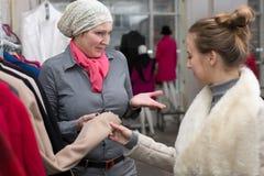 Vendedora que mostra a variedade de revestimentos ao cliente na loja Imagem de Stock