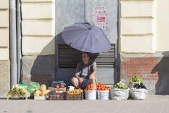 Vendedores do mercado de rua da manhã com os vegetais caseiros frescos no centro da cidade Lviv, Ucrânia Homem que vende o alimen Imagens de Stock Royalty Free