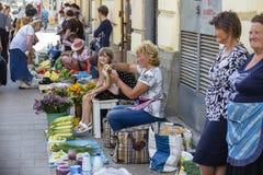 Vendedores do mercado de rua da manhã com os vegetais caseiros frescos no centro da cidade Lviv, Ucrânia Mulheres que vendem o al Foto de Stock