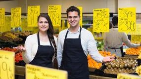 Vendedores jovenes positivos que ofrecen el buen precio para las frutas Fotografía de archivo libre de regalías