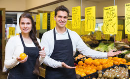 Vendedores jovenes sonrientes que ofrecen el buen precio para las frutas Imagen de archivo