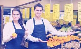 Vendedores jovenes sonrientes que ofrecen el buen precio para las frutas Imagenes de archivo