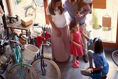 Vendendo a bicicleta - mulher do vendedor a vender a bicicleta nova da família nova na loja fotografia de stock