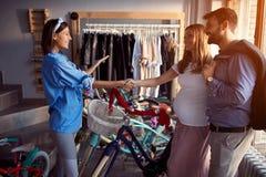 Vendendo a bicicleta - mulher do vendedor a vender a bicicleta nova dos clientes na loja imagem de stock royalty free