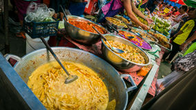 Vender selling variety of  foods and  fresh vegetables local market. Stock Image