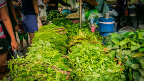 Vender selling variety of  foods and  fresh vegetables local market. Stock Photos