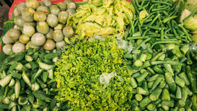 Vender selling variety of  foods and vegetables local market. Royalty Free Stock Photography