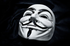 Vendetta mask on black background . This mask is a well-known symbol for the online hacktivist Stock Images