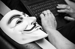 Vendetta mask on old armchair in abandoned  factory with woman on background with computer Royalty Free Stock Images
