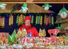 Vendeur à la stalle avec les sucreries colorées sur le marché de Noël de Vilnius Image libre de droits