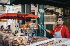 Vendeur à un stand de nourriture de tête de pain sur le marché de ville, Londres, R-U images stock
