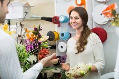 Vendeur aidant à sélectionner des fleurs Images stock