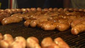 Vendeur asiatique de mouvement lent faisant cuire la saucisse grillante populaire de BBQ March? de nuit clips vidéos